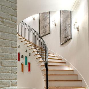 На фото: большая изогнутая лестница в стиле современная классика с деревянными ступенями, крашенными деревянными подступенками и металлическими перилами