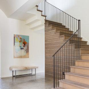 Idee per una grande scala sospesa minimalista con pedata in legno, alzata in legno, parapetto in metallo e pareti in legno