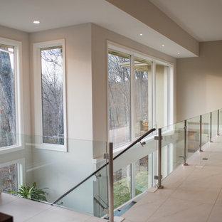 Immagine di una scala minimalista di medie dimensioni con pedata in legno, nessuna alzata e parapetto in vetro