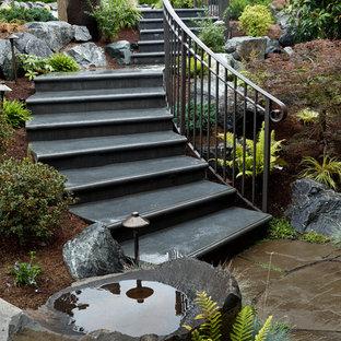 Ejemplo de escalera curva, clásica, grande, con escalones de hormigón y barandilla de metal