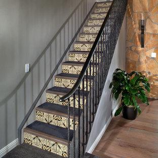 Diseño de escalera minimalista con escalones enmoquetados, contrahuellas con baldosas y/o azulejos y barandilla de metal