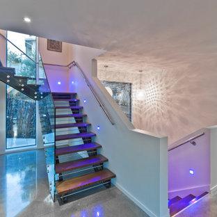 На фото: большая угловая лестница в современном стиле с деревянными ступенями, стеклянными подступенками и стеклянными перилами