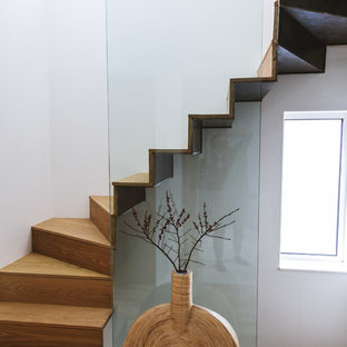 Contemporary wood curved glass railing staircase in London with wood risers.