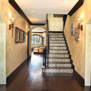 Ejemplo de escalera mediterránea con escalones de madera y contrahuellas con baldosas y/o azulejos