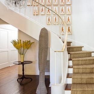 Idee per una grande scala curva classica con pedata in legno e alzata in legno verniciato