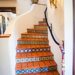 Bild på en medelhavsstil svängd trappa i terrakotta, med sättsteg i kakel