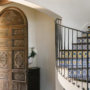 Diseño de escalera de caracol con escalones de madera, contrahuellas con baldosas y/o azulejos y barandilla de metal