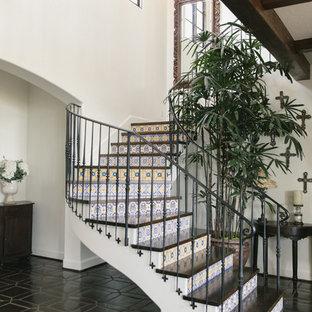 Foto de escalera curva, mediterránea, con escalones de madera, contrahuellas con baldosas y/o azulejos y barandilla de metal