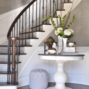 Diseño de escalera curva, clásica, con escalones de madera, contrahuellas con baldosas y/o azulejos y barandilla de varios materiales