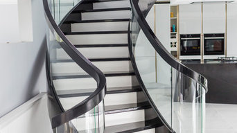 black and white curved stairs with glass balustrade