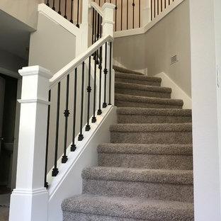 Ejemplo de escalera curva, de estilo americano, de tamaño medio, con escalones enmoquetados, contrahuellas enmoquetadas y barandilla de madera