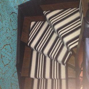 ロンドンの中くらいのカーペット敷きのトランジショナルスタイルのおしゃれな直階段 (カーペット張りの蹴込み板、木材の手すり) の写真