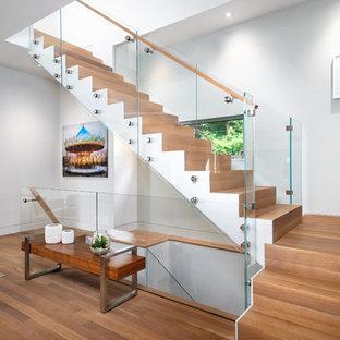 ニューヨークの中サイズの木のコンテンポラリースタイルのおしゃれなかね折れ階段 (木の蹴込み板、ガラスの手すり) の写真