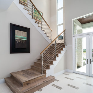 Inspiration for a large transitional wooden u-shaped cable railing staircase remodel in Miami with wooden risers
