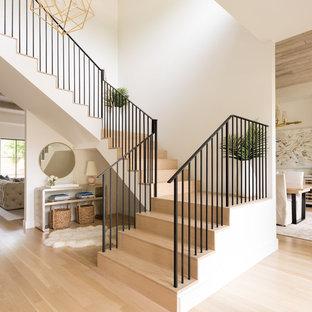 Пример оригинального дизайна: угловая лестница среднего размера в современном стиле с деревянными ступенями, деревянными подступенками и металлическими перилами