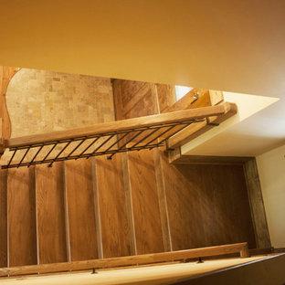 シャーロットの中サイズの木のラスティックスタイルのおしゃれな折り返し階段 (木の蹴込み板、金属の手すり) の写真