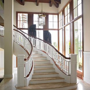 マイアミの中くらいのタイルのトランジショナルスタイルのおしゃれなサーキュラー階段 (フローリングの蹴込み板、木材の手すり) の写真