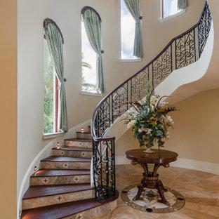 Imagen de escalera curva, bohemia, con escalones de madera y contrahuellas con baldosas y/o azulejos