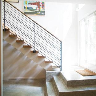Immagine di una scala sospesa minimalista con pedata in legno, alzata in ardesia e parapetto in cavi