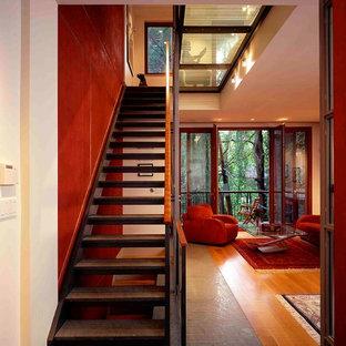 Immagine di una scala a rampa dritta minimalista di medie dimensioni con pedata in legno e nessuna alzata