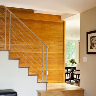 Foto de escalera moderna con escalones de madera, contrahuellas de madera y barandilla de metal