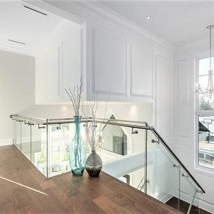 バンクーバーの中くらいのガラスのコンテンポラリースタイルのおしゃれな折り返し階段 (ガラスの蹴込み板、金属の手すり) の写真