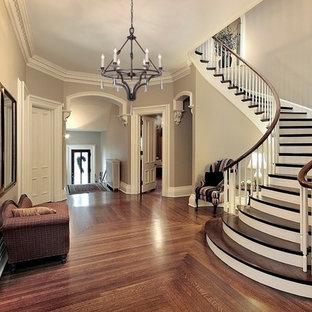 Стильный дизайн: изогнутая лестница среднего размера в стиле неоклассика (современная классика) с деревянными ступенями, деревянными подступенками и деревянными перилами - последний тренд