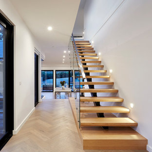 This is an example of a contemporary wood floating staircase in Melbourne with open risers and glass railing.