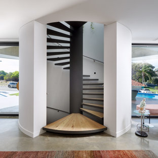 Expansive contemporary wood spiral staircase in Perth with open risers and metal railing.