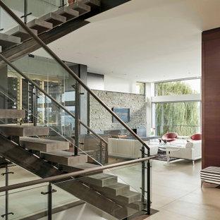 Inspiration för en mellanstor funkis flytande betongtrappa, med öppna sättsteg och räcke i glas