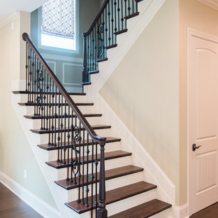 Large transitional wooden curved wood railing staircase photo in Baltimore with painted risers