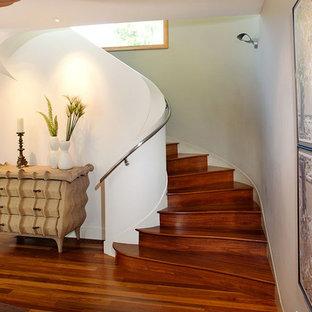 Foto de escalera curva, contemporánea, de tamaño medio, con escalones de madera, contrahuellas de madera y barandilla de metal