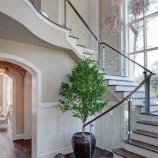 Modelo de escalera clásica renovada con escalones de madera, contrahuellas de madera pintada y barandilla de vidrio