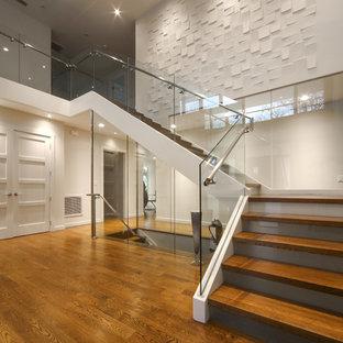 Bild på en stor funkis l-trappa i trä, med sättsteg i glas och räcke i glas