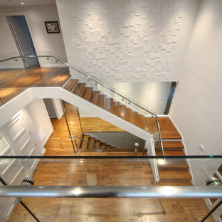 Inspiration for a large modern wooden l-shaped glass railing staircase remodel in New York with glass risers