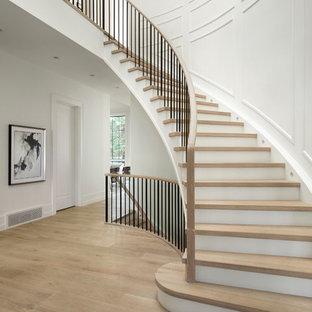 Modelo de escalera curva, clásica renovada, con escalones de madera, contrahuellas de madera pintada y barandilla de varios materiales