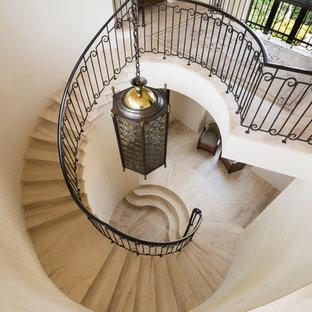 ヒューストンの巨大な地中海スタイルのおしゃれなサーキュラー階段 (金属の手すり) の写真