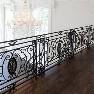 Ejemplo de escalera curva, mediterránea, grande, con escalones de madera, contrahuellas de madera pintada y barandilla de varios materiales