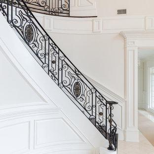 Ejemplo de escalera curva, mediterránea, grande, con escalones de madera y barandilla de metal
