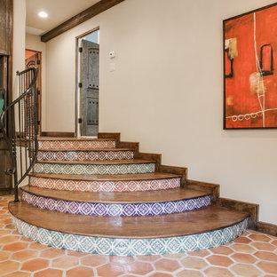 Modelo de escalera curva, mediterránea, grande, con escalones de madera, contrahuellas con baldosas y/o azulejos y barandilla de metal