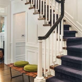 Ejemplo de escalera en L, clásica renovada, de tamaño medio, con escalones de madera y contrahuellas de madera pintada
