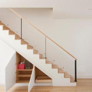 Foto di una scala a rampa dritta minimalista di medie dimensioni con pedata in legno, alzata in legno e parapetto in cavi