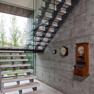 Esempio di una piccola scala sospesa minimalista con pedata in pietra calcarea, alzata in pietra calcarea e parapetto in vetro