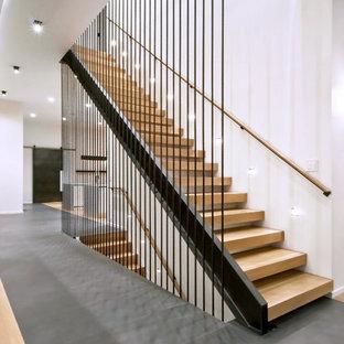 Bild på en mellanstor industriell rak trappa i trä, med öppna sättsteg och räcke i metall