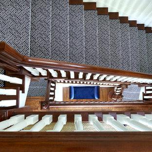 Modelo de escalera en L y boiserie, tradicional, con escalones de madera, contrahuellas de madera pintada, barandilla de madera y boiserie