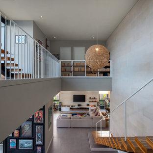 Неиссякаемый источник вдохновения для домашнего уюта: большая лестница в стиле модернизм с деревянными ступенями, деревянными подступенками, металлическими перилами и кирпичными стенами