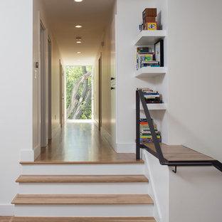 Foto på en liten funkis rak trappa i trä, med sättsteg i målat trä och räcke i metall