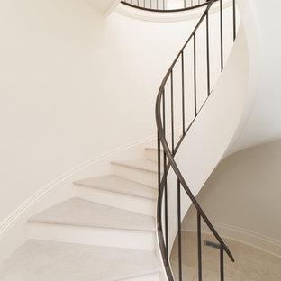 Ejemplo de escalera curva, mediterránea, grande, con escalones de piedra caliza y contrahuellas de madera
