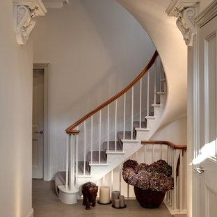 На фото: изогнутая лестница в классическом стиле с крашенными деревянными ступенями и крашенными деревянными подступенками с