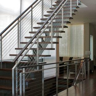 Immagine di una grande scala a rampa dritta minimalista con pedata in legno e alzata in vetro